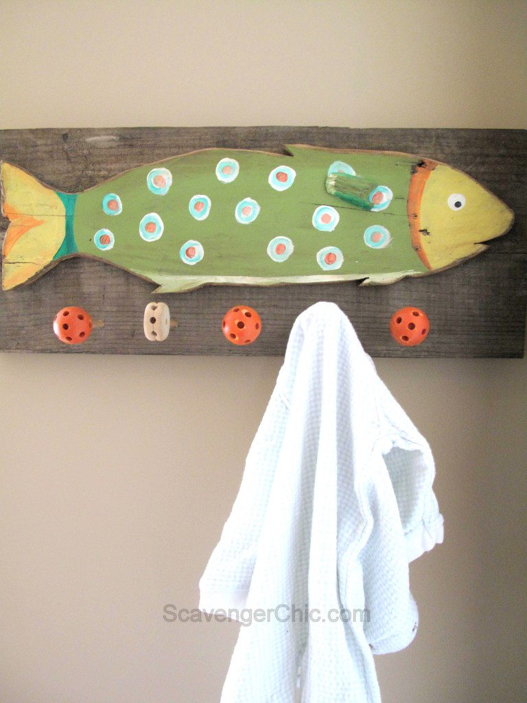 Reclaimed wood coat rack made from pallet wood with a colorful fish theme and tinker toys for hooks. Step by step directions. #MyRepurposedLife #reclaimed #wood #coatrack #tinkertoys via @repurposedlife