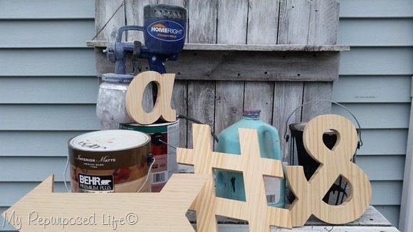 Finish Max paints wooden symbols