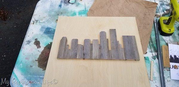 rustic skyline artwork placed on plywood