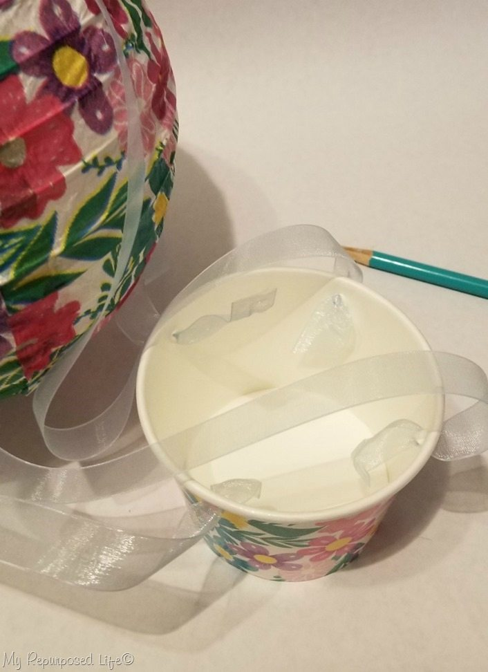 use pencil point to push ribbon through cardboard candy cup