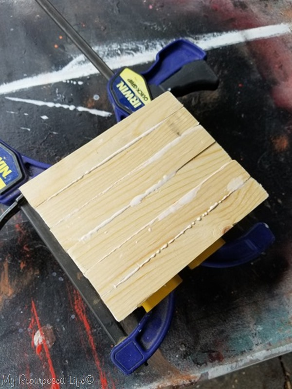 clamp blocks of square wood to make geometric candle holder