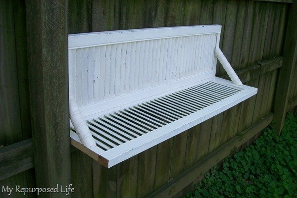 bi-fold door shelf hanging on fence