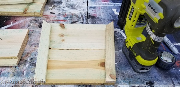 nail gun adds support pieces to wooden planter box