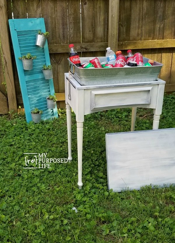 How to make a drink station out of a sewing machine cabinet. I found the perfect insert to use to hold the ice and beverages. Doubles as a side table. #MyRepurposedLife #repurposed #furniture #sewingcabinet #drinkstation #outdoors #diy via @repurposedlife