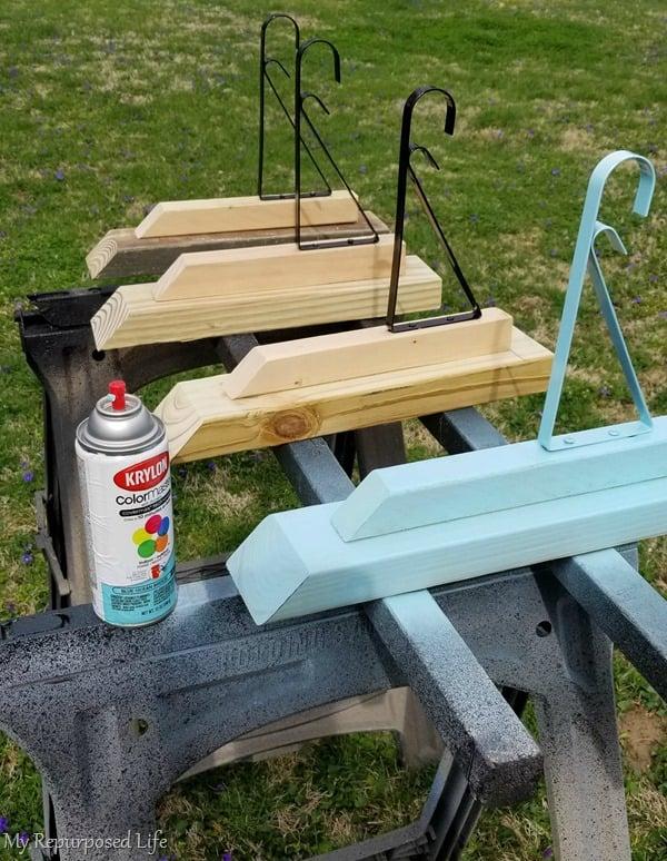 spray paint wooden diy brackets that hold dollar store metal brackets on whiskey barrel planter posts