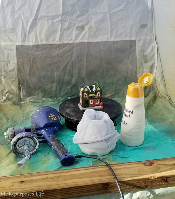 using a small spray shelter to paint a Christmas Village white