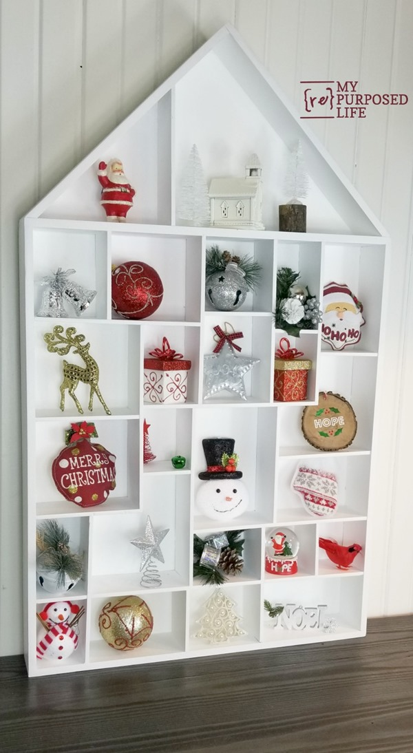 House Shaped Cubby Shelf for Christmas or everyday collectibles. With 25+ cubbies, easily use this as an advent calendar. Two different tutorials to follow to customize this to your liking. #MyRepurposedLife #Christmas #decor #wallshelf #cubby #advent  via @repurposedlife