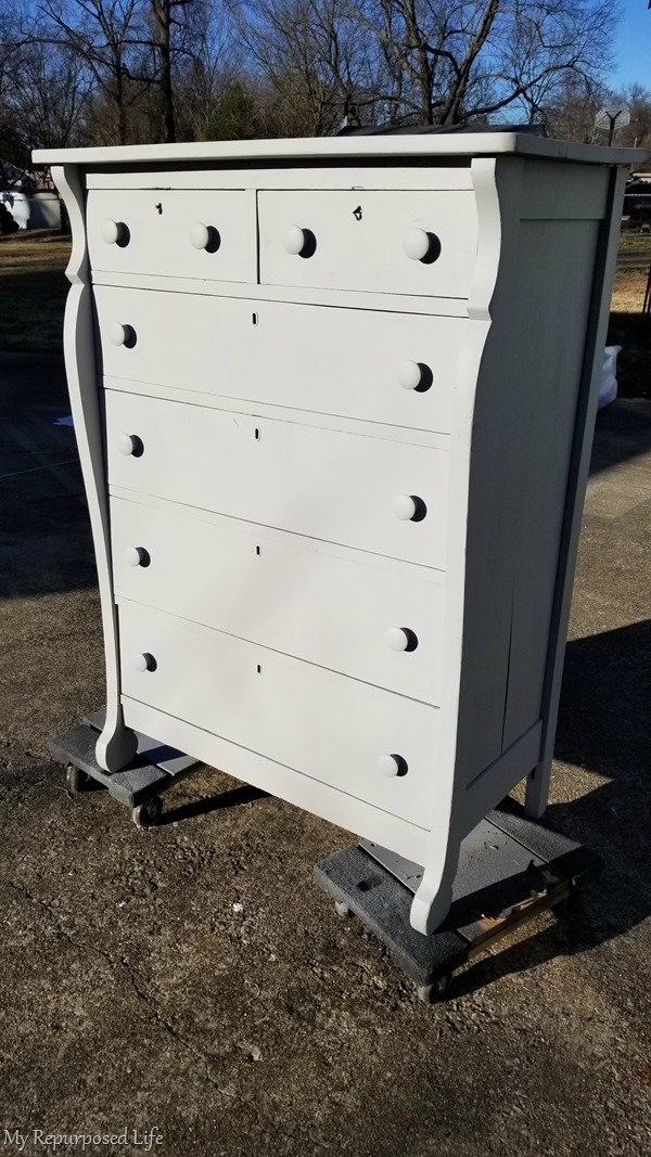 move antique chest of drawers on furniture dollies to dry in the sun