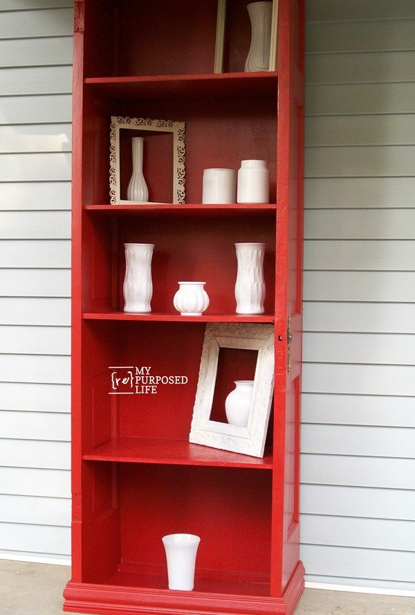repurposed door bookshelf with white glassware