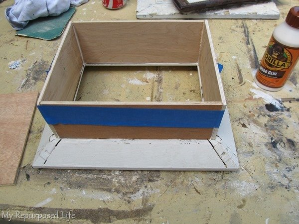 painters tape holds shadow box pieces while gluing