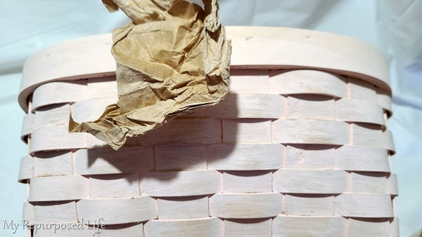 sanding milk paint wicker basket with brown craft paper