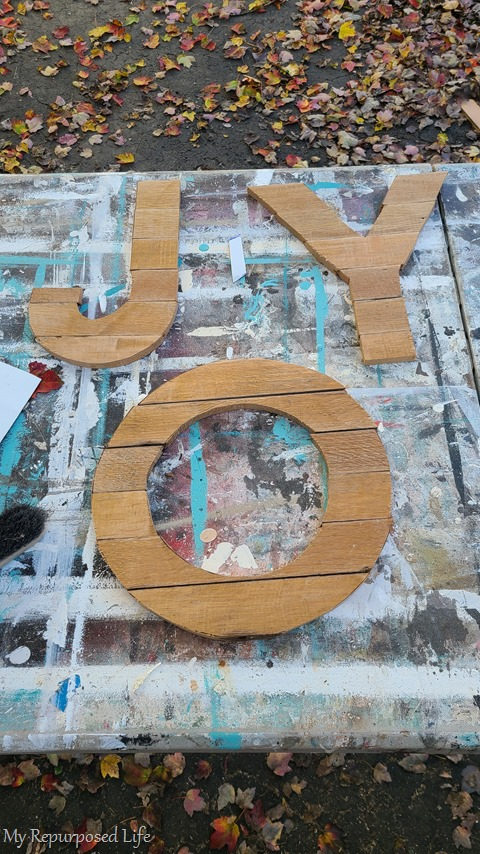 joy letters cut out of reclaimed wooden flooring
