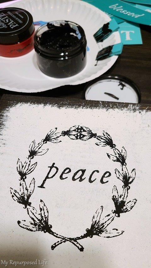 scrap wood block with wreath and the word peace