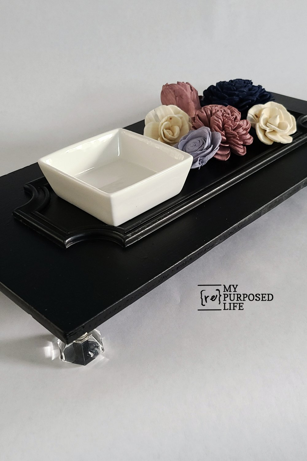 How to make a cabinet door vanity tray in six easy steps using paint and reclaimed glass knobs. Step by step directions to do it yourself. #MyRepurposedLife #repurposed #cabinetdoor #vanitytray #diy #easy #thriftstore #makeover via @repurposedlife